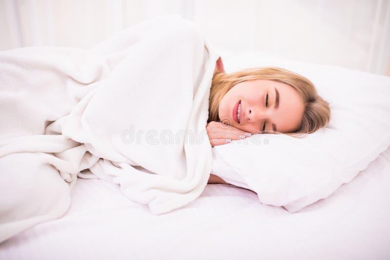 Femme avec de longs cheveux blancs se situant et dormant dans le lit photo stock