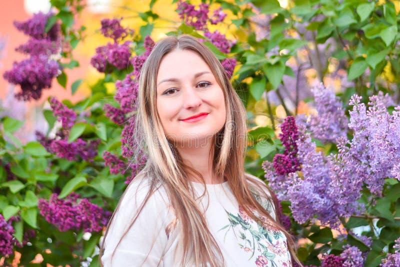 Femme avec de longs cheveux blonds dans le jardin avec des fleurs belle fille un jour ensoleill? photographie stock