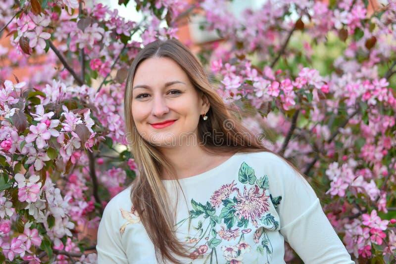 Femme avec de longs cheveux blonds dans le jardin avec des fleurs belle fille un jour ensoleill? photos stock