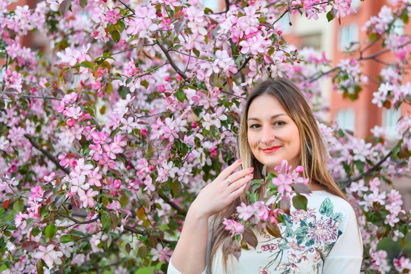Femme avec de longs cheveux blonds dans le jardin avec des fleurs belle fille un jour ensoleill? photo libre de droits