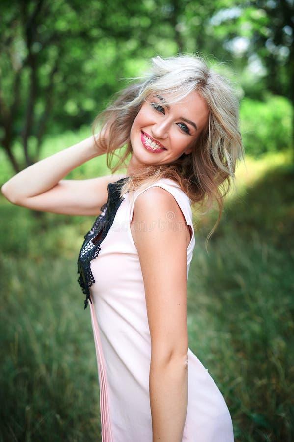 Femme avec de longs cheveux blonds posant en parc d'été photos libres de droits