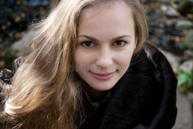Femme avec de longs cheveux dans le manteau de fourrure noir photographie stock libre de droits