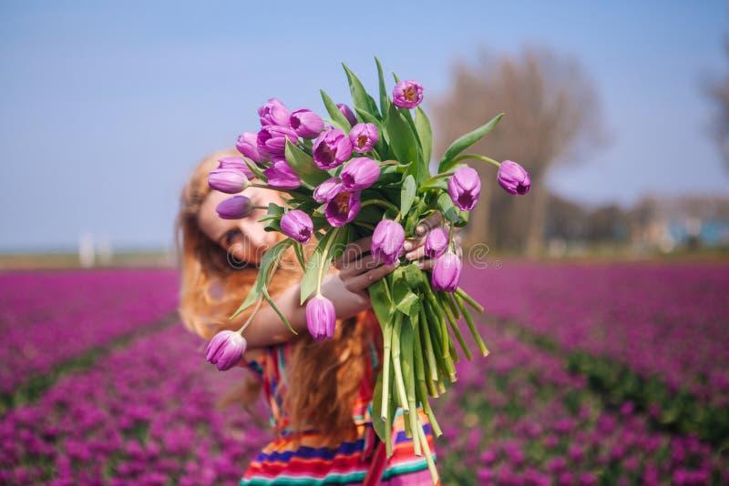 Femme avec de longs cheveux rouges portant une robe rayée tenant un bouquet des fleurs pourpres de tulipes sur le fond sur les ch image libre de droits
