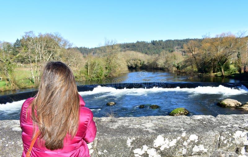 Femme avec de longs cheveux sur un pont regardant la vue Rivière, cascade et forêt avec le ciel bleu Ponte Maceira, Espagne photos libres de droits