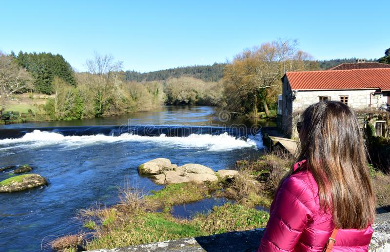 Femme avec de longs cheveux sur un pont regardant la vue Rivière, cascade et forêt avec le ciel bleu Ponte Maceira, Espagne images libres de droits