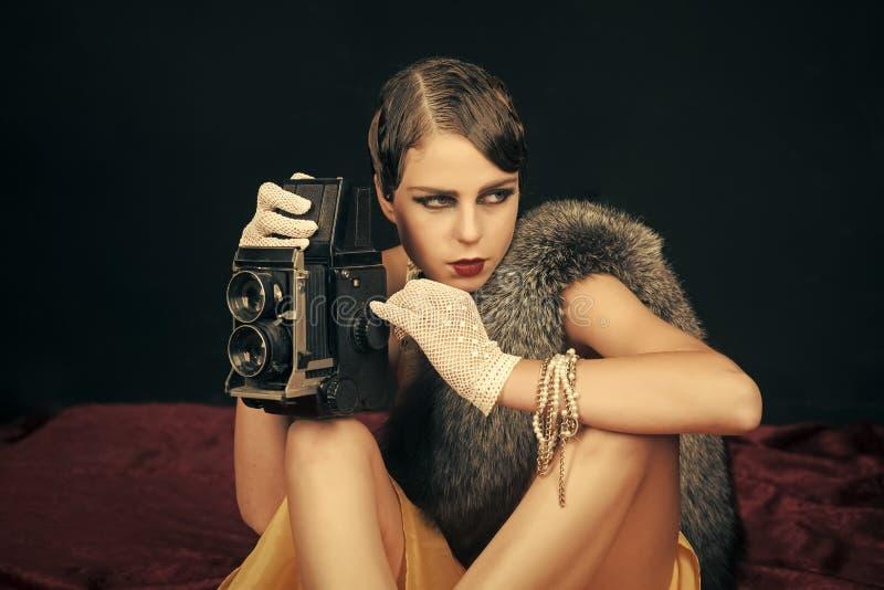 Femme avec de rétros cheveux, maquillage et vieil appareil-photo image libre de droits