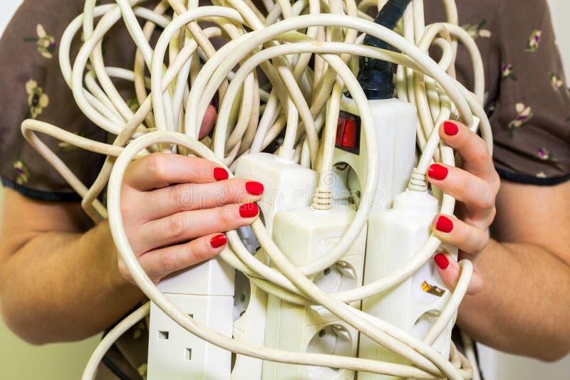 Femme avec de vieilles et peu sûres cordes électriques de bande d'extension photo stock