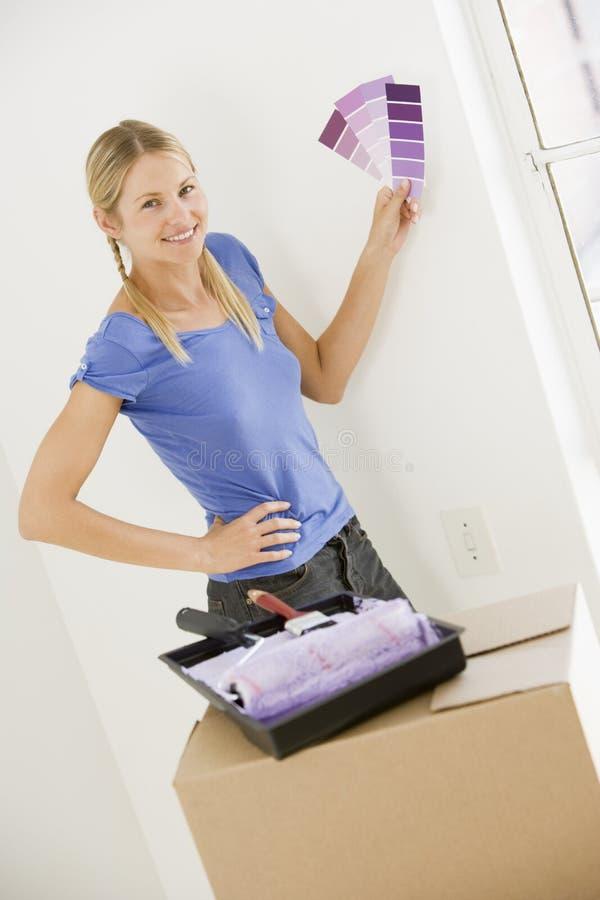 Femme avec des échantillons de peinture dans le sourire à la maison neuf photos stock