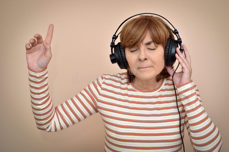 Femme avec des écouteurs et des yeux fermés appréciant la musique images libres de droits