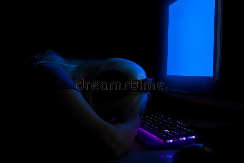 Femme avec des écouteurs se trouvant sur ses mains sur le clavier devant le moniteur de PC photographie stock libre de droits
