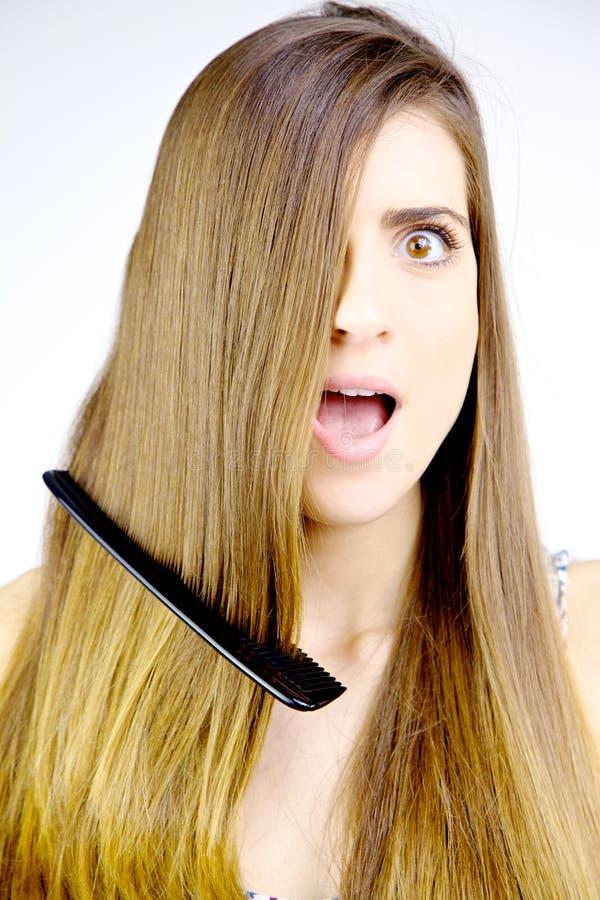 Femme avec des actions de peigne dans des cris de cheveux effrayés images stock