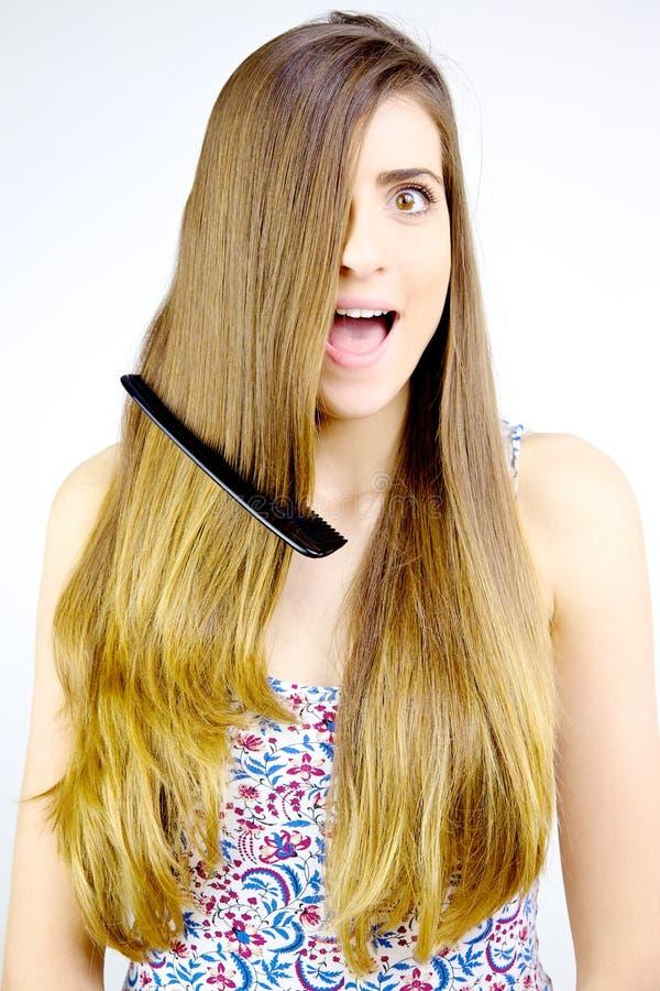 Femme avec des actions de peigne dans les cheveux criant le tir moyen effrayé photographie stock