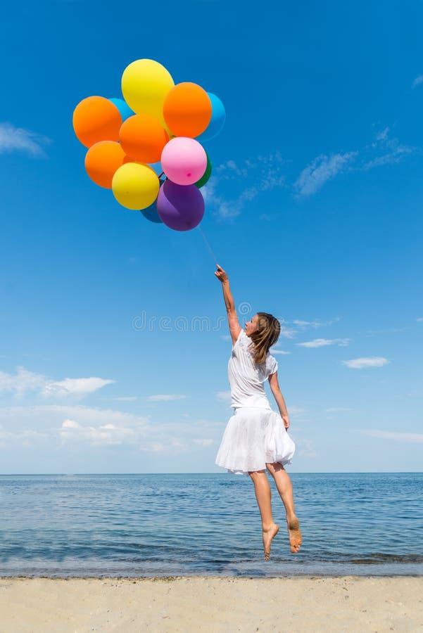 Femme avec des baloons sautant sur la mer photo libre de droits