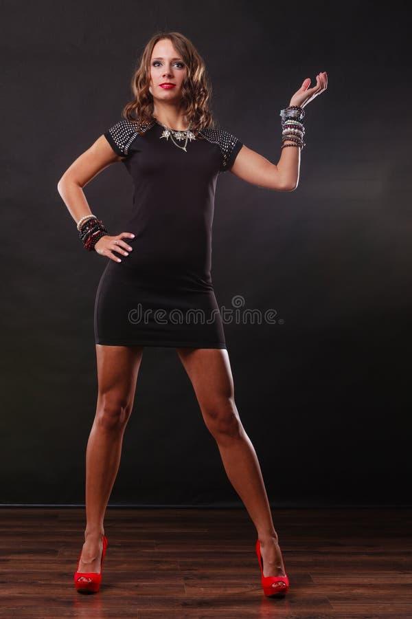 Femme avec des bijoux dans la robe de soirée noire images stock