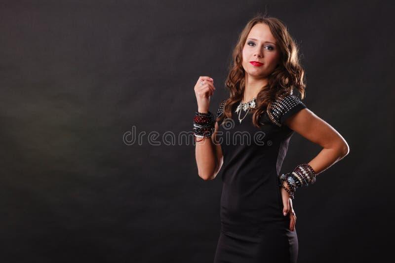 Femme avec des bijoux dans la robe de soir?e noire photographie stock