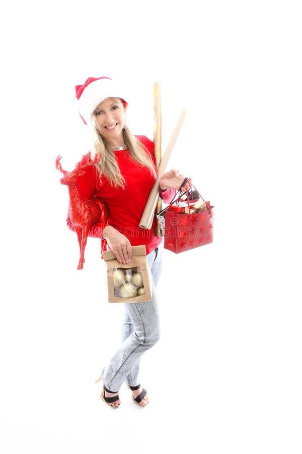 Femme avec des bras pleins de l'achat de choses de Noël photos stock
