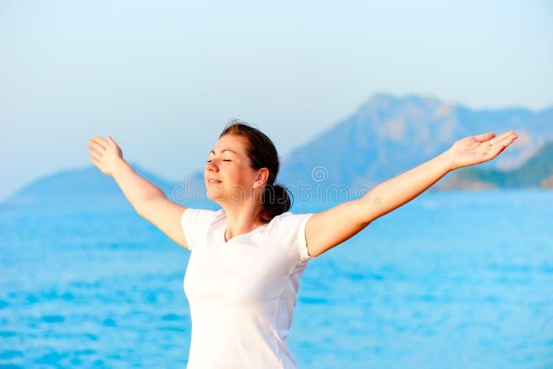 Femme avec des bras tendus appréciant le soleil photographie stock
