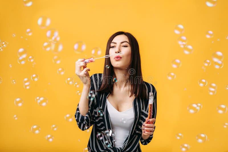 Femme avec des bulles de savon, fond jaune photos stock