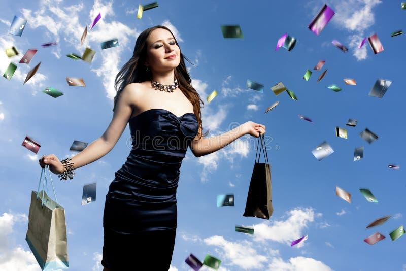 Femme avec des cartes de crédit pleuvant au-dessus de elle photos stock