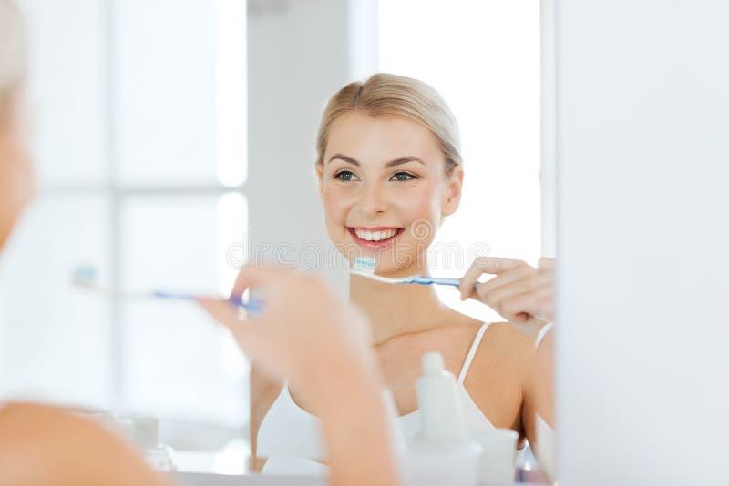 Femme avec des dents de nettoyage de brosse à dents à la salle de bains image stock