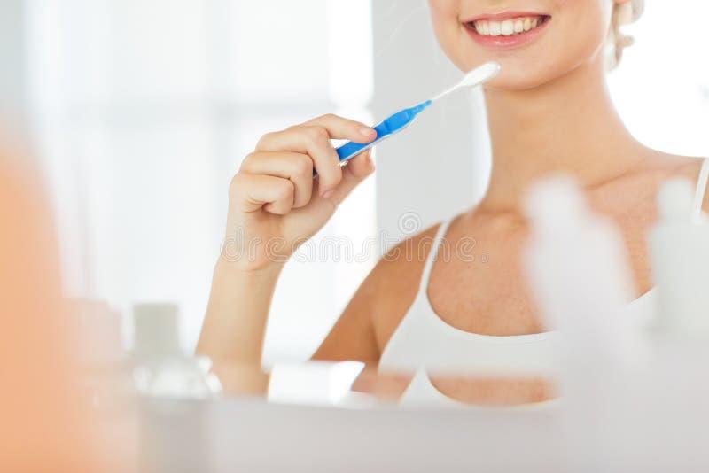 Femme avec des dents de nettoyage de brosse à dents à la salle de bains photos libres de droits