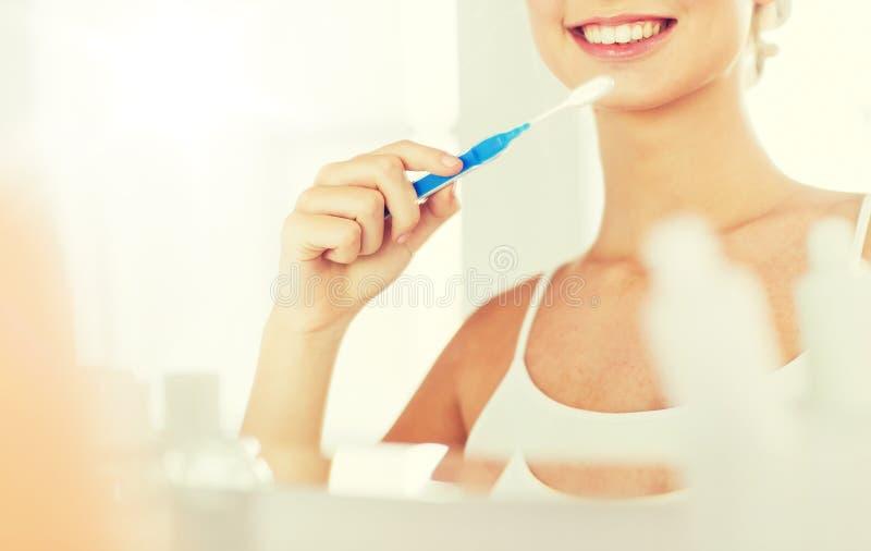Femme avec des dents de nettoyage de brosse à dents à la salle de bains images libres de droits