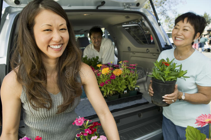 Femme avec des fleurs de chargement de mère dans la voiture photo stock