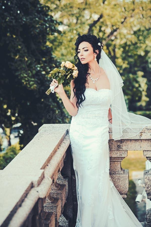 Femme avec des fleurs sur le balcon Femme sensuelle avec le bouquet de mariage Fille de beauté avec le maquillage et la coiffure  photo libre de droits