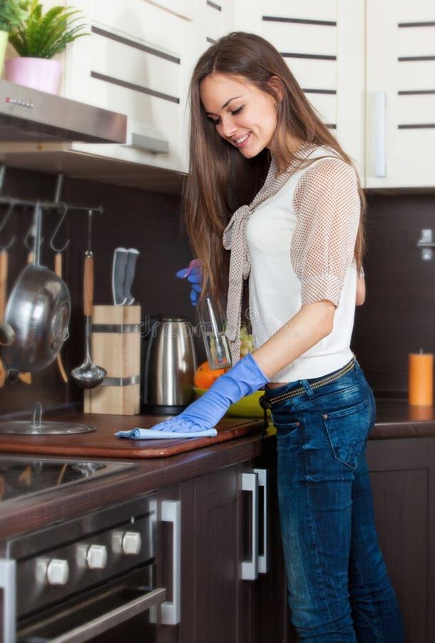 Femme avec des gants nettoyant la cuisine images libres de droits