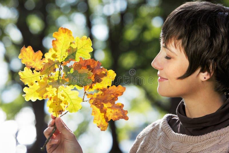 Femme avec des lames d'automne photo libre de droits