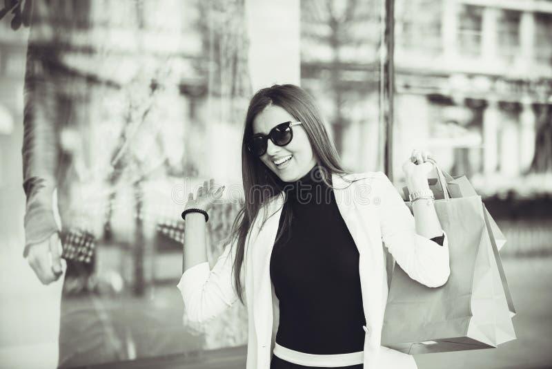Femme avec des paniers entrant dans la boutique photo libre de droits