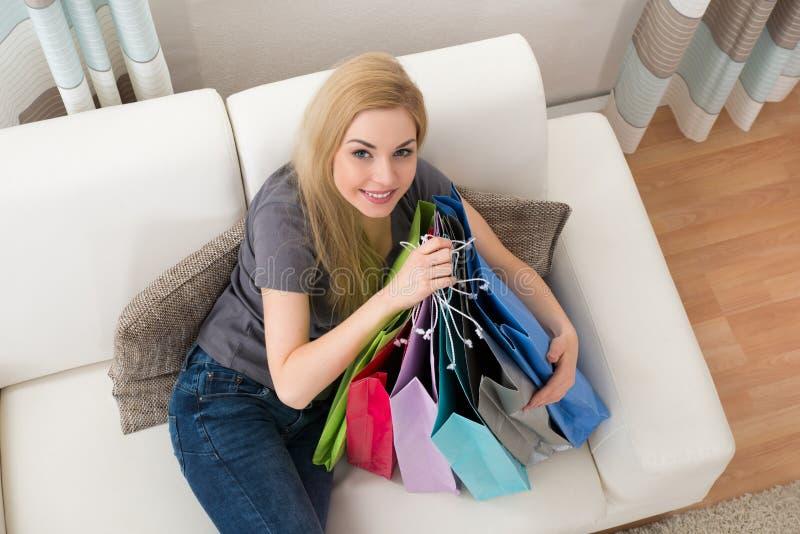 Femme avec des paniers sur le divan image stock