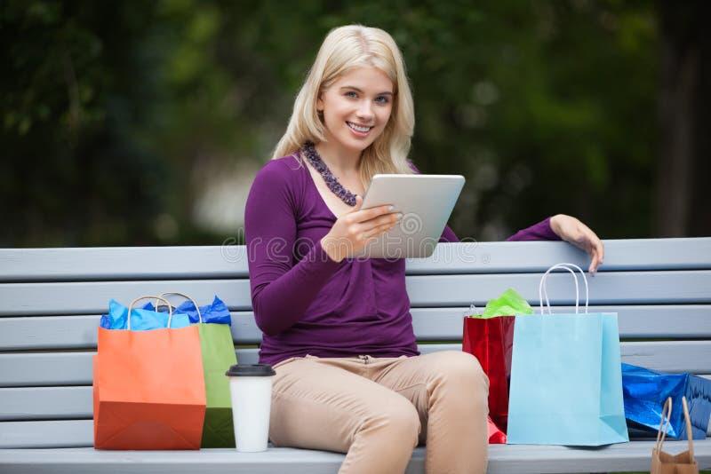 Femme avec des paniers utilisant la tablette dehors photos stock