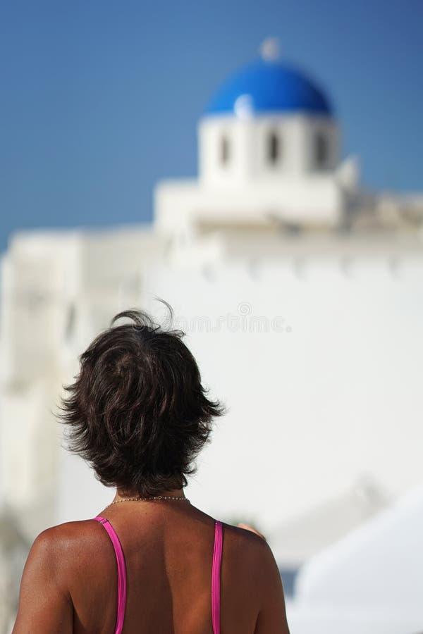Femme avec des regards fuchsia de robe à un dôme d'une église à Oia, Santorini image libre de droits