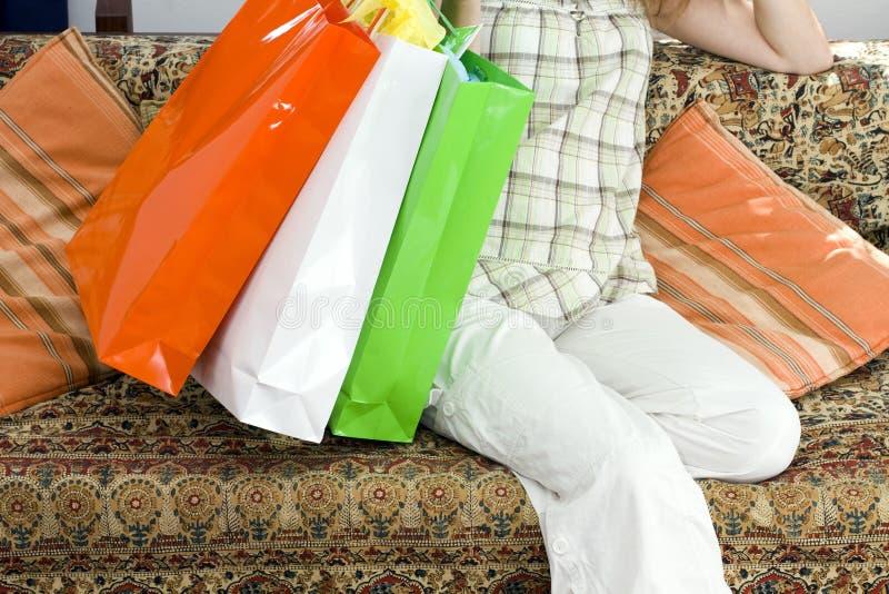 Femme avec des sacs à provisions se reposant sur un divan photos stock