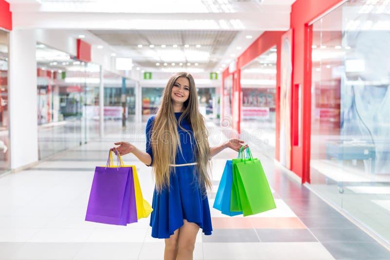 Femme avec des sacs en papier posant dans le grand mail images stock