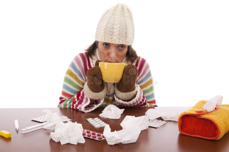 Femme avec des sympt40mes de grippe buvant une boisson chaude photo libre de droits