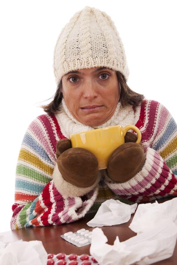 Femme avec des sympt40mes de grippe buvant une boisson chaude photographie stock