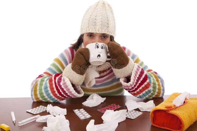 Femme avec des sympt40mes de grippe buvant une boisson chaude image stock