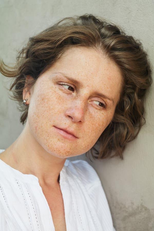 Femme avec des taches de rousseur regardant vers le bas images stock