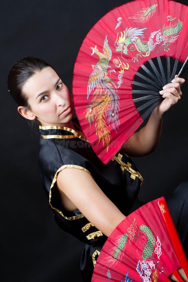 Femme avec des ventilateurs de rouge de fu de kung images stock