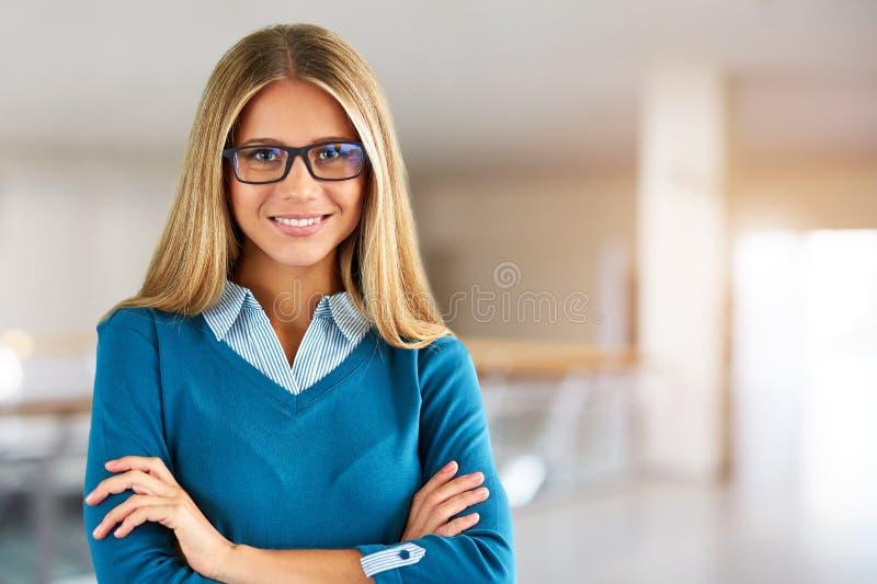 Femme avec des verres au centre d'affaires avec les mains croisées photographie stock