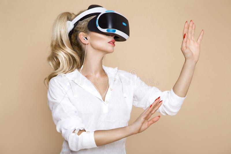 Femme avec des verres de VR de réalité virtuelle Jeune fille dans le casque augmenté virtuel de réalité Casque de VR photographie stock libre de droits