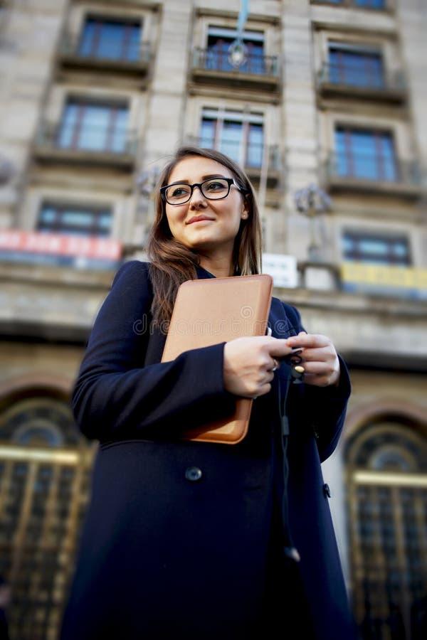 Femme avec des verres se tenant dans la ville avec le comprimé numérique photo stock