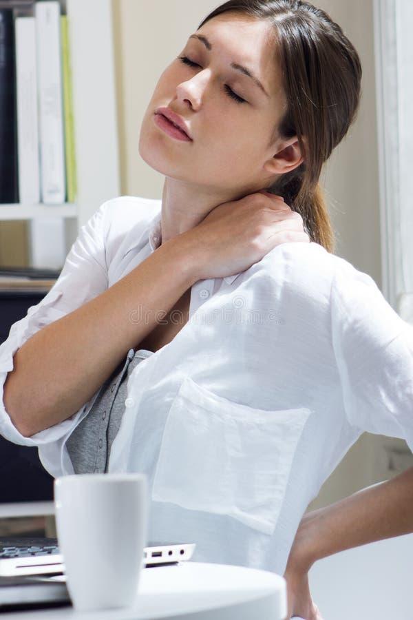 Femme avec douleurs de dos au travail photos libres de droits