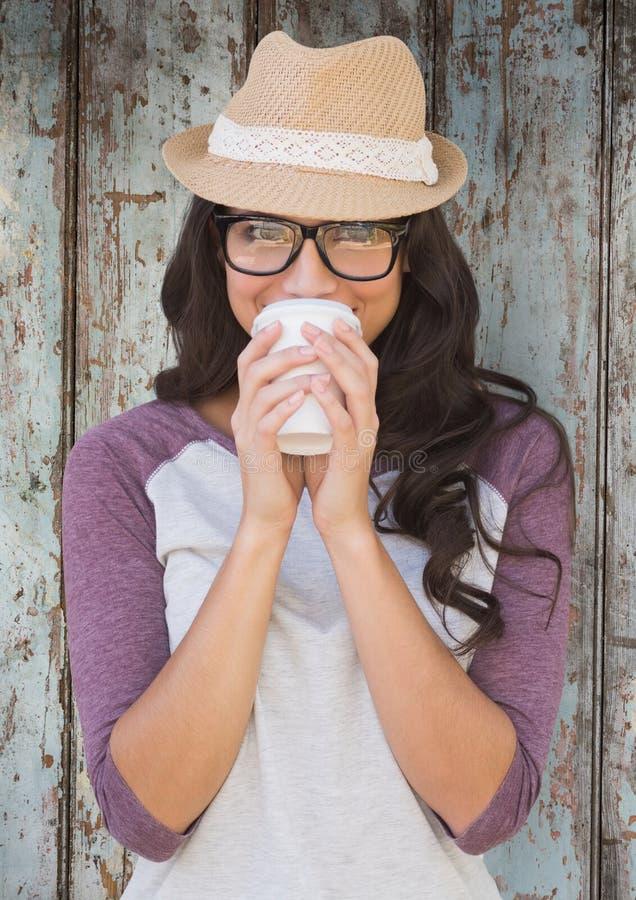 Femme avec du café et le chapeau contre le panneau en bois illustration stock