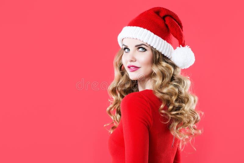 Femme avec du charme avec de longs cheveux bouclés et maquillage dans un chapeau de Santa image libre de droits