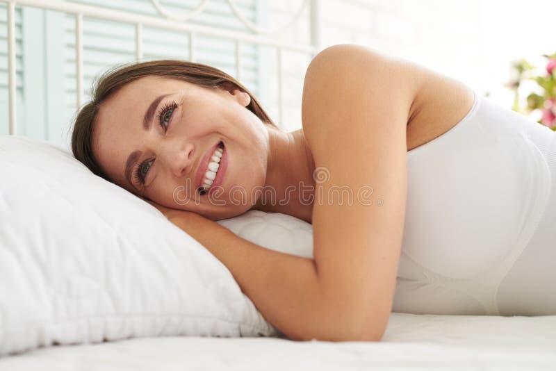 Femme avec du charme de sourire se trouvant sur le lit photo stock