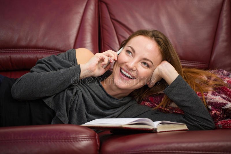 Femme avec du charme gaie se trouvant et parlant au téléphone portable photographie stock