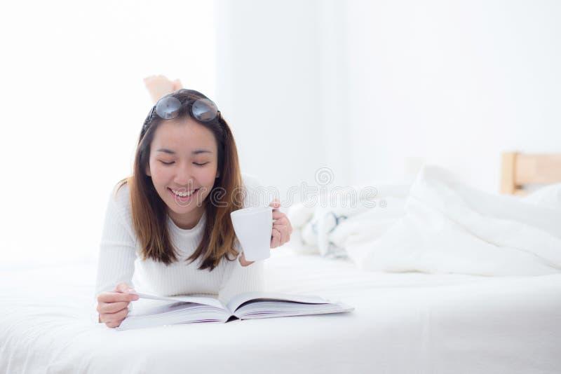 Femme avec du charme se trouvant sur le lit lisant un livre et tenant la tasse de café regardant dans l'appareil-photo dans la ch image libre de droits